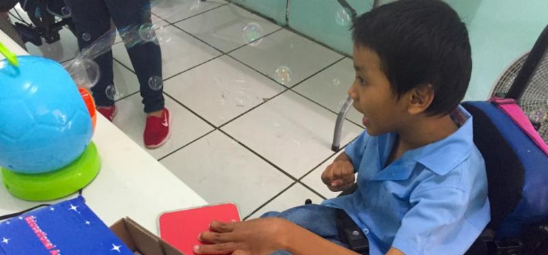 A boy watches with excitement as he presses a red_ rectangular switch_ triggering a small_ round_ blue bubble machine to blow bubbles toward him.