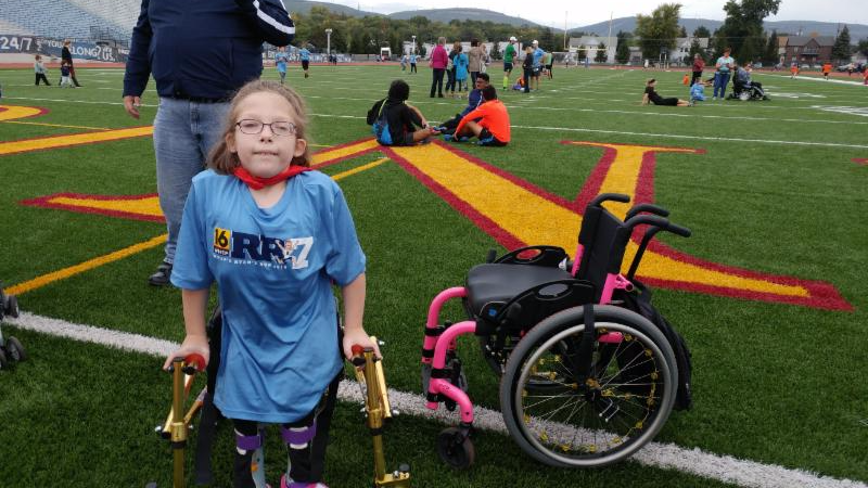 Helen stands in a sports field using her gold walker_ with her pink manual wheelchair next to her.