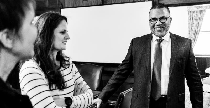 Black and white photos of two smiling women and a man in a business suit while standing and talking in a board room.