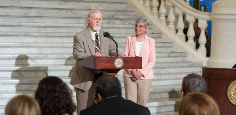 A man in a suit stands at a podium in front of marble steps addressing the crowd_ and a woman in a pink blazer stands next to him_ smiling.