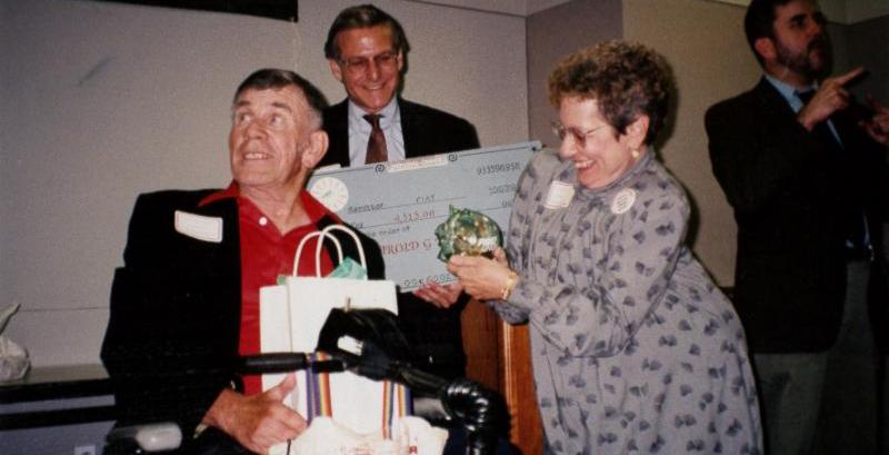 A man sits in a wheelchair with gift bags on his lap_ a woman stands next to him handing him a full_ glass piggy bank_ and a man stands behind them smiling_ holding a large check.