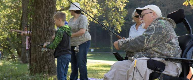 Older man sits in a his power wheelchair adjusting his fishing rod. Two women and a boy are behind him in the grass_ the boy is also fishing.