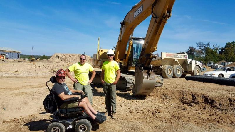 Bob and two workmen at a worksite with a backhoe in the background. Bob sits in his all-terrain wheelchair.