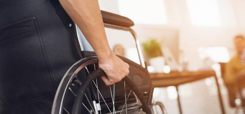 A man sits in a wheelchair with his hand on the wheel.