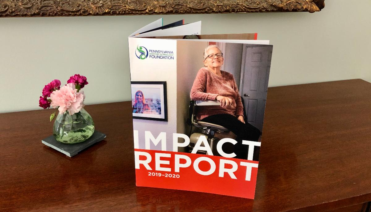 PATF 2019-2020 Impact Report is propped on a table next to a small vase of flowers.