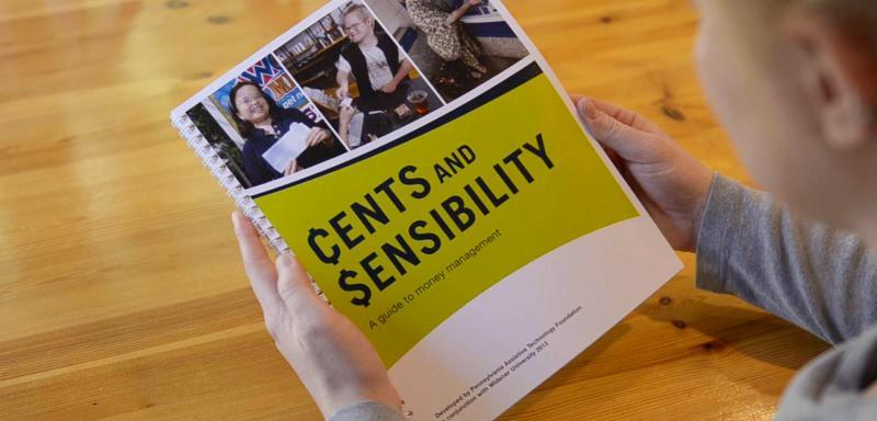 Cents and Sensibility book cover held by person at a table.