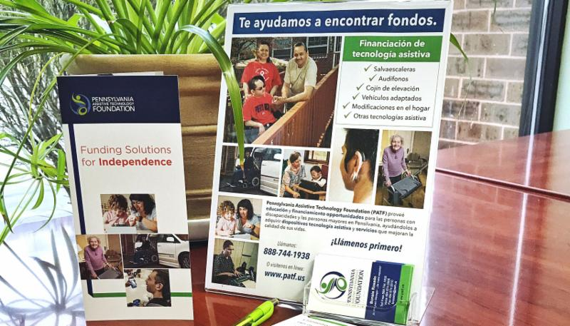 Brochure and flyer stand on top of a desk in front of a plant. The brochure reads_ Funding Solutions for Independence and the flyer reads_ Te ayudamos a encontrar fondos.