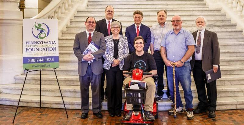 8 people pose next to a PATF poster in front of a marble staircase_ one of them seated in a red scooter_ the rest standing.