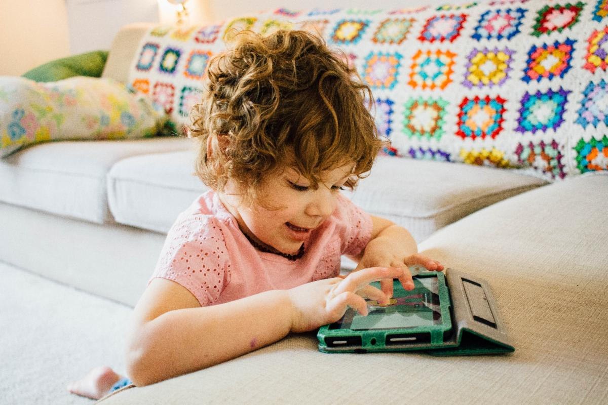 Young girl smiles while tapping the screen of a tablet
