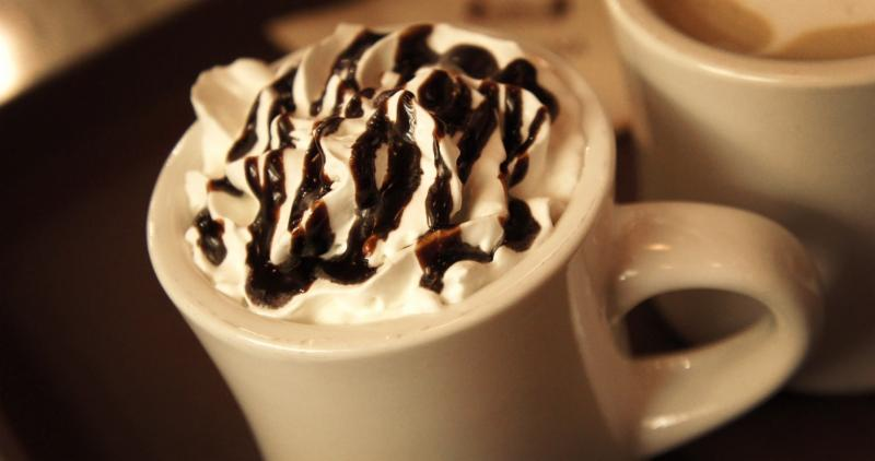 Mug with whipped cream on top_ drizzled with chocolate syrup.