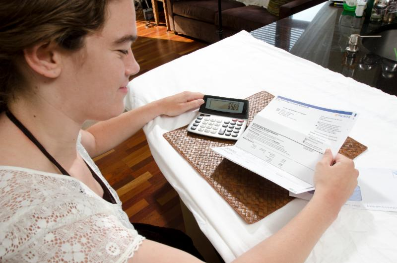 Young woman looks at her bank statement and a calculator while sitting at a table.