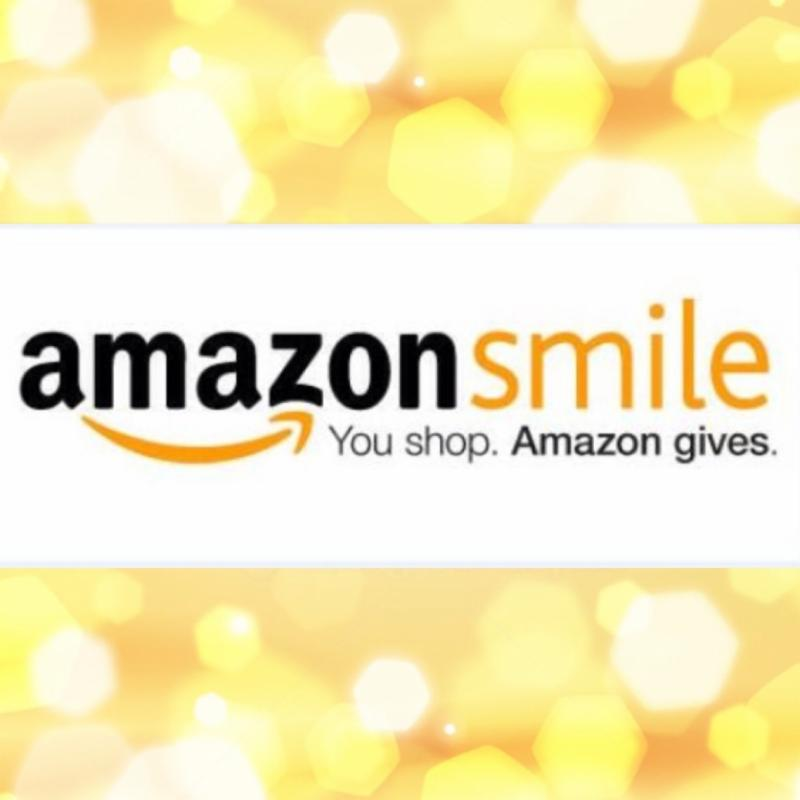 AmazonSmile logo with soft yellow glowing lights behind it.