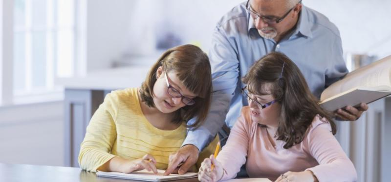 A father and two daughters with down syndrome doing homework. The girls are sitting at a table_ writing with pencils. Father is standing behind them with an open book in his hand.