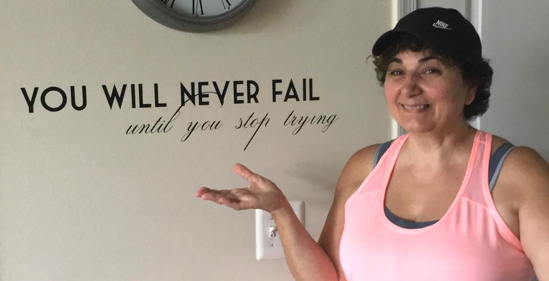 Susie stands smiling next to a wall decal motioning her hand toward it that reads You will never fail until you stop trying.