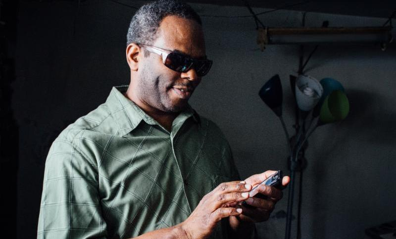 Man wearing sunglasses holds a smart phone and feels the screen with his other hand.
