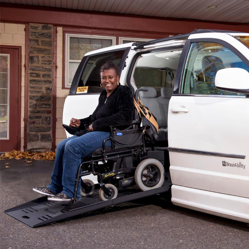 A woman drives her power wheelchair down the ramp of her adapted van.