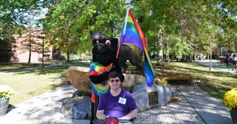 Young man smiles and sits on his motorized scooter in front of panther mascot on a sunny college campus. Panther is wearing a rainbow tie-dye t-shirt and holding a rainbow flag.