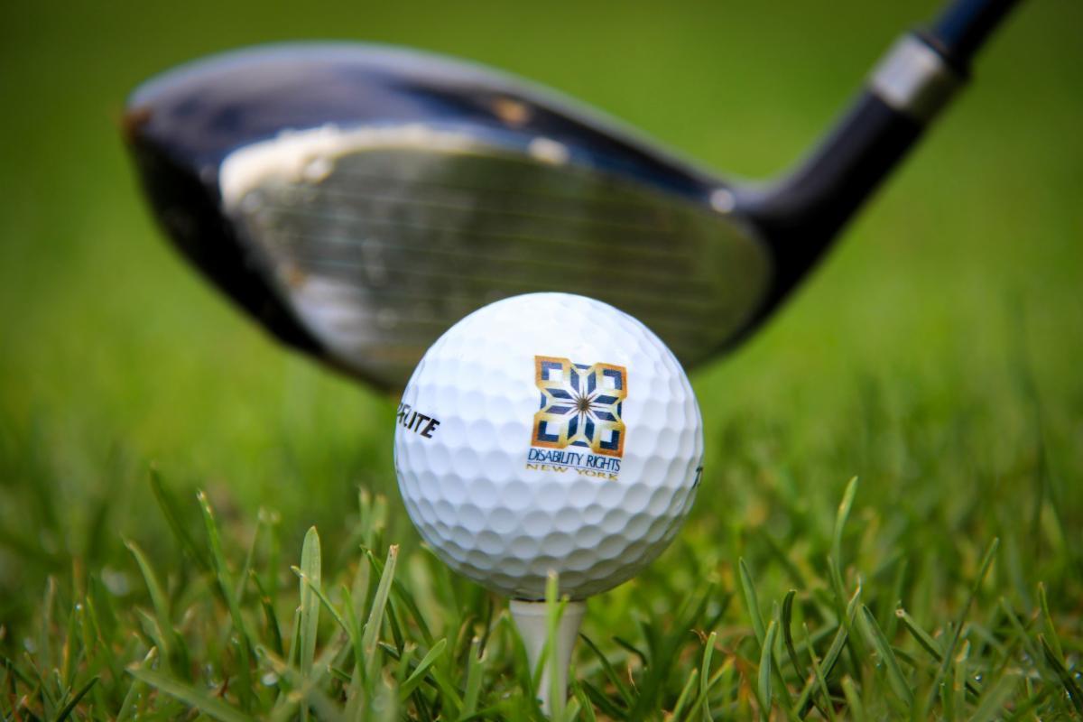 golf club head behind a golf ball with DRNY on it