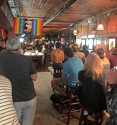 several people in Stonewall Inn listening to presentation  - rainbow flags hanging from ceiling