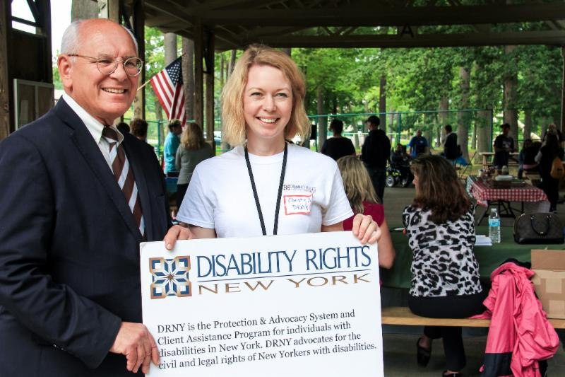 Man in a suit with glasses standing next to a woman in a white tee shirt at a picinic holding a sign that says Disability Rights New York