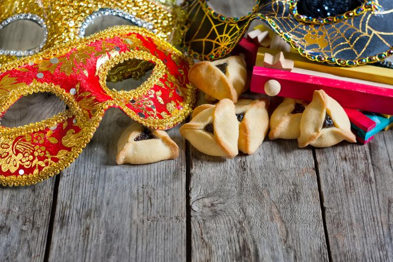 Hamantaschen cookies or Haman s ears noisemaker and carnival masks for Purim celebration  jewish holiday . Copy space background.