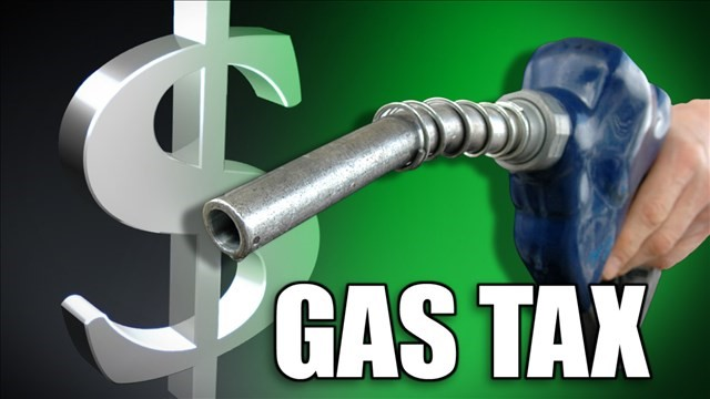 Dollar sign gas nozzle with blue handle that a left hand is clutching with the words gas tax below