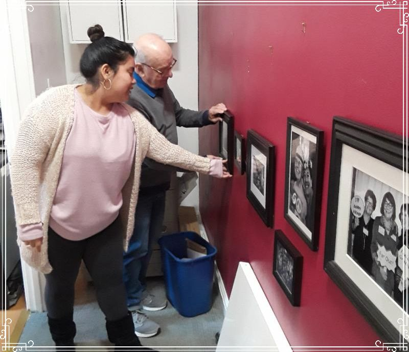 Office corps volunteer Andrina helping Bill with the newest photo installment.