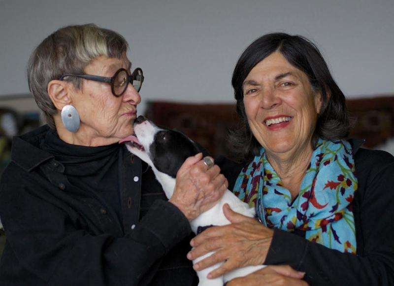 Two women smiling and playing with a white and black dog