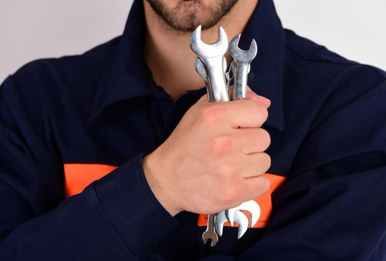 Spanner instruments for fixing or tightening details. Maintenance and repairing concept. Man holds wrench tool isolated on white background. Mechanic or plumber with metallic spanner equipment in hand