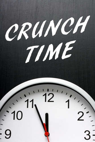 The phrase Crunch Time in white text on a blackboard above a clock with the hands pointing at midnight or twelve