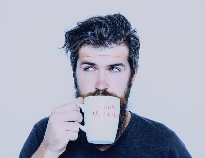 handsome bearded man with stylish hair beard and mustache on serious face in shirt holding white cup or mug with good morning text drinking tea or coffee in studio on grey background