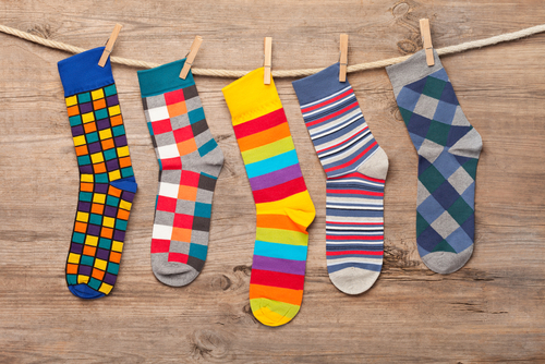 Multi colored socks on wooden background. This file is cleaned and retouched.