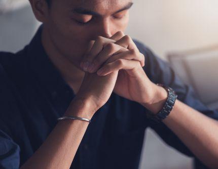 Christian faith towards God concept_ Asian man christians worship and pray in church