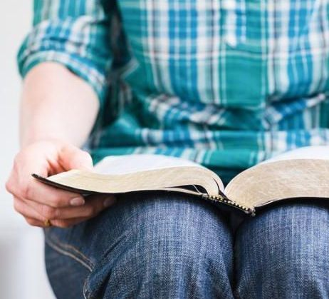 A young woman at home holds an open Bible in her lap. Closeup image with shallow DOF focus on the tip of the book.