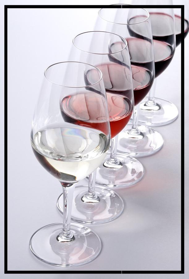Row of glass filled with white ros  and red wines.