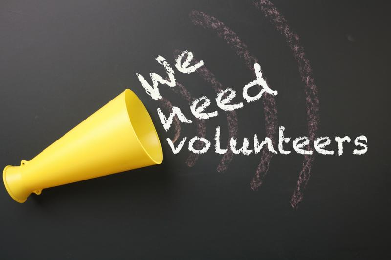 megaphone with message we need volunteers on the blackboard