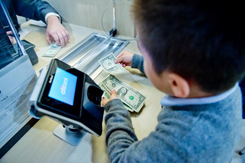A small child hands dollar bills through a bank teller window