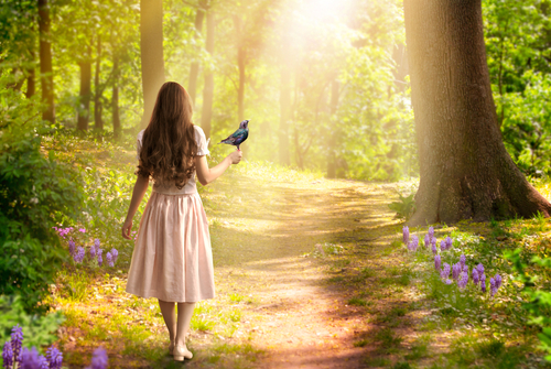Lady girl with long hair in dress with bird in hand walking in fantasy enchanted fairy tale spring forest with blooming flowers and sun rays_ mysterious road goes through trees in magical elvish wood