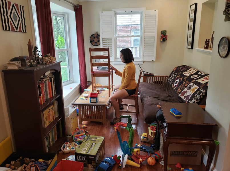 Mother working from messy room