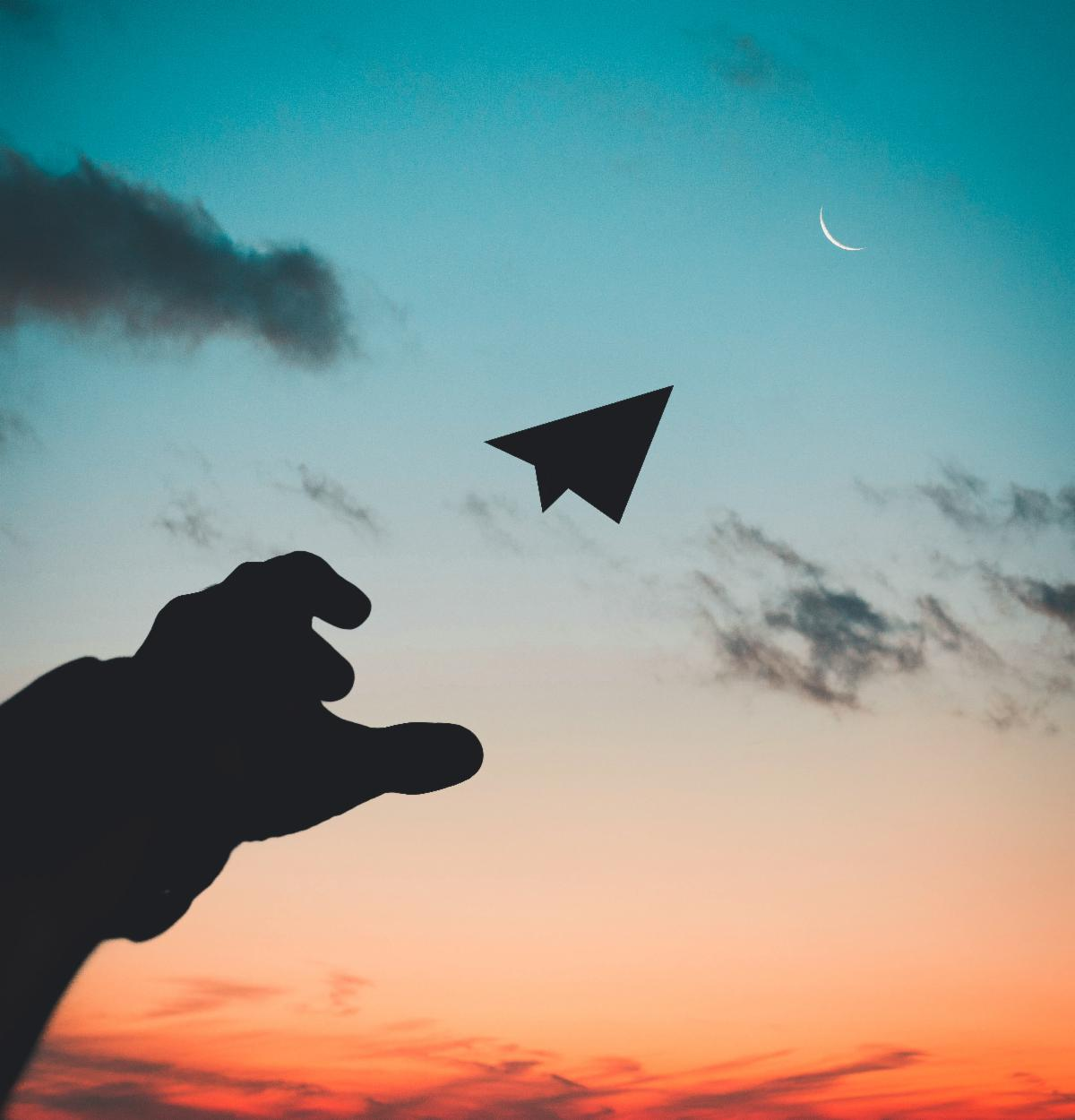 Paper airplane sailing toward moon