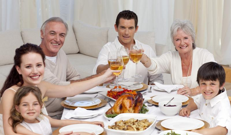 Happy family testing with wine in a dinner at home