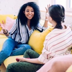 African American woman with delightful smile gesturing while telling exciting story to female friend relaxing on yellow cozy sofa at home