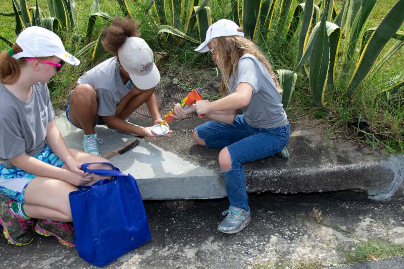 Volunteers labeling storm drain inlet