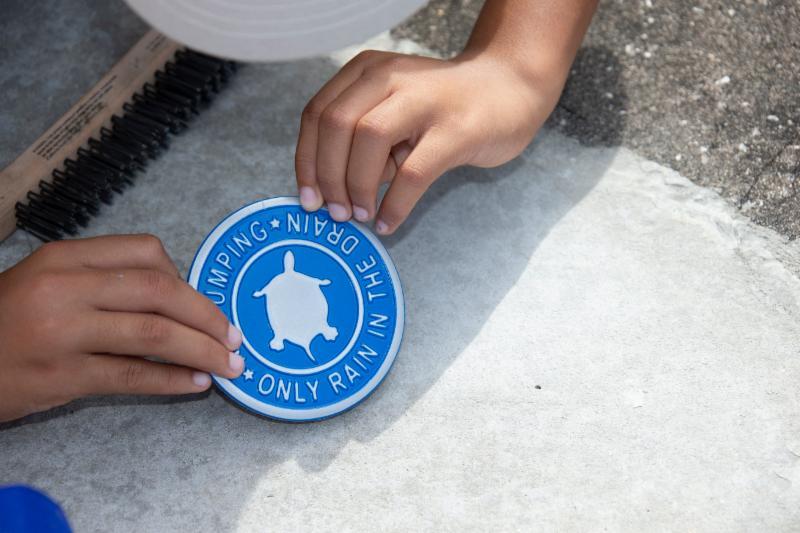 Volunteer Holding storm drain label