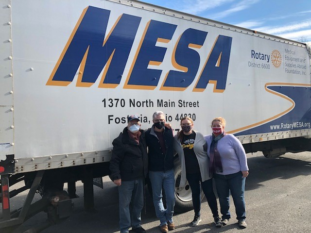 """Image of 4 people standing in front of large bus that reads """"MESA"""""""