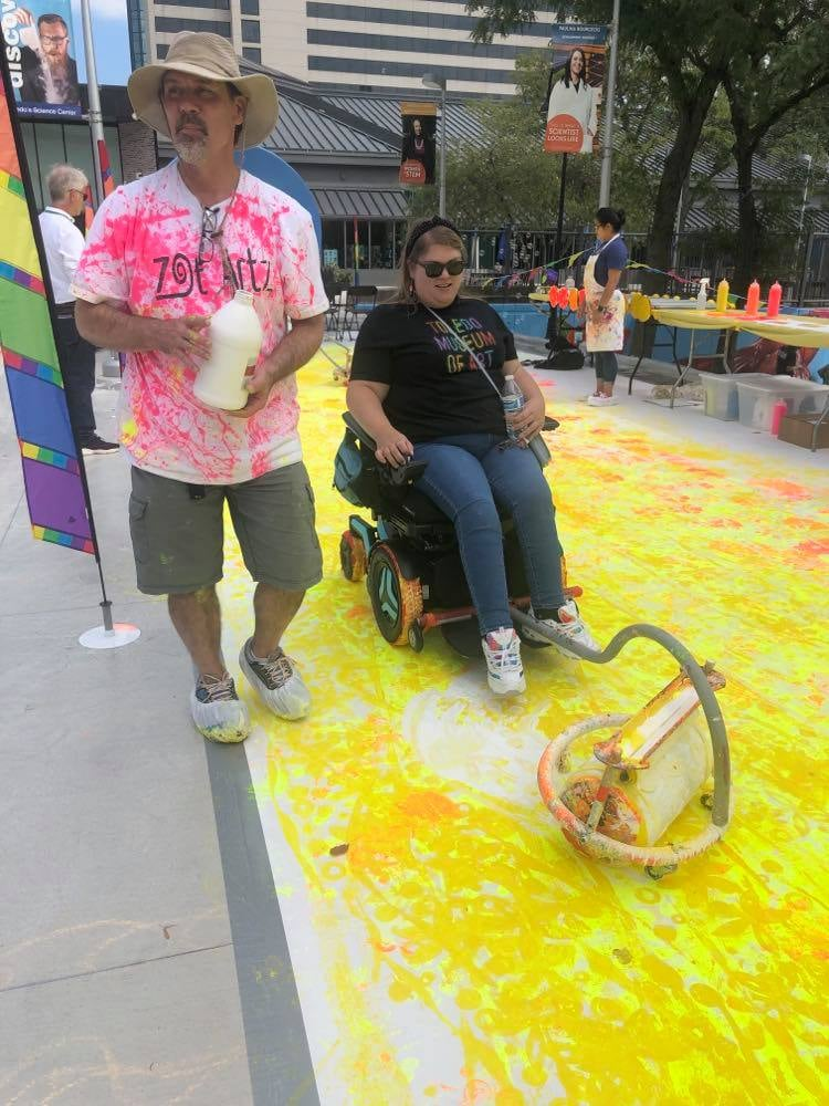 Woman in wheelchair painting with wheelchair