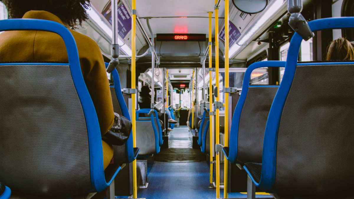 Back of a bus with blue floor and yellow handles