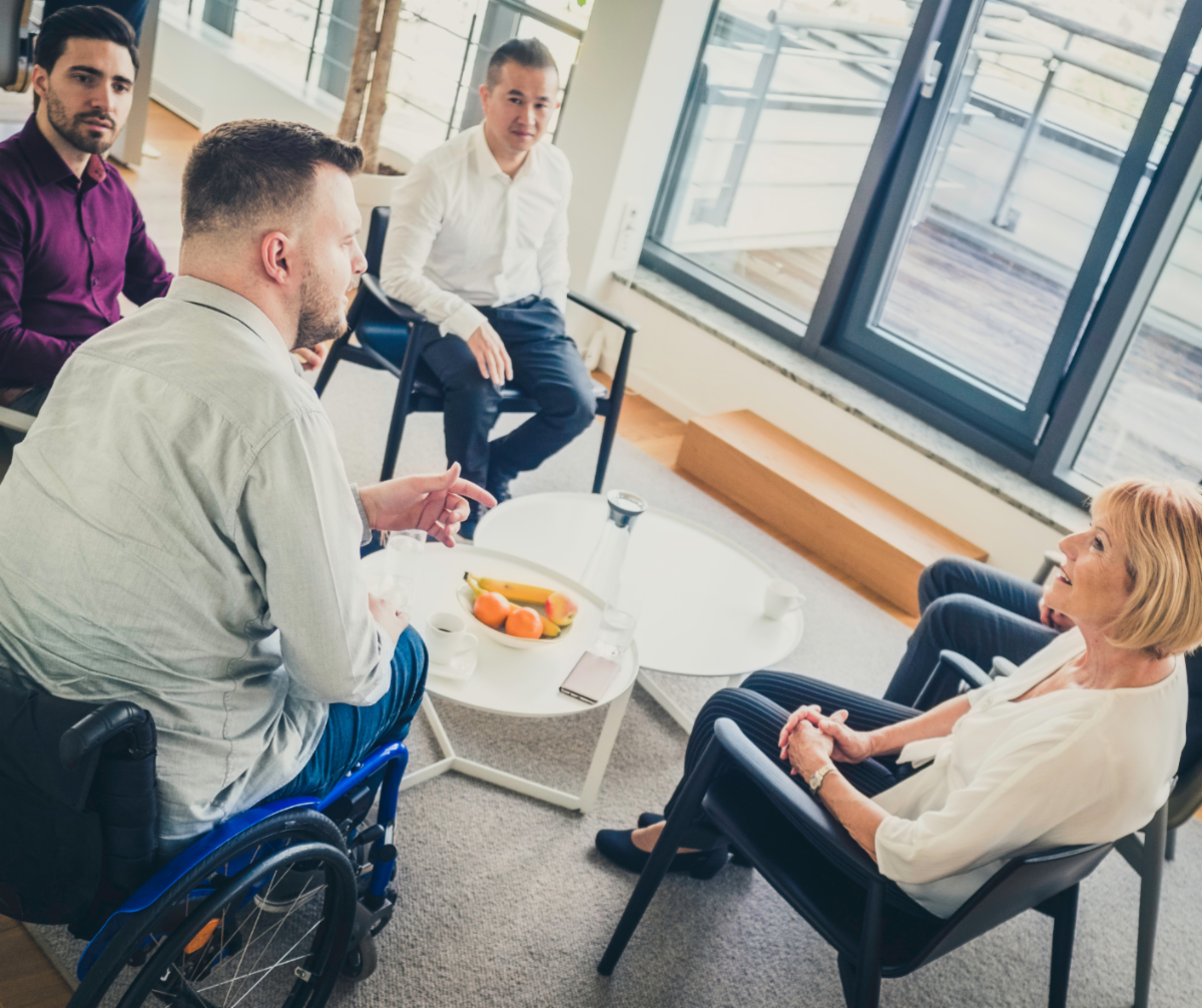 4 people sitting around a table one person in wheelchair
