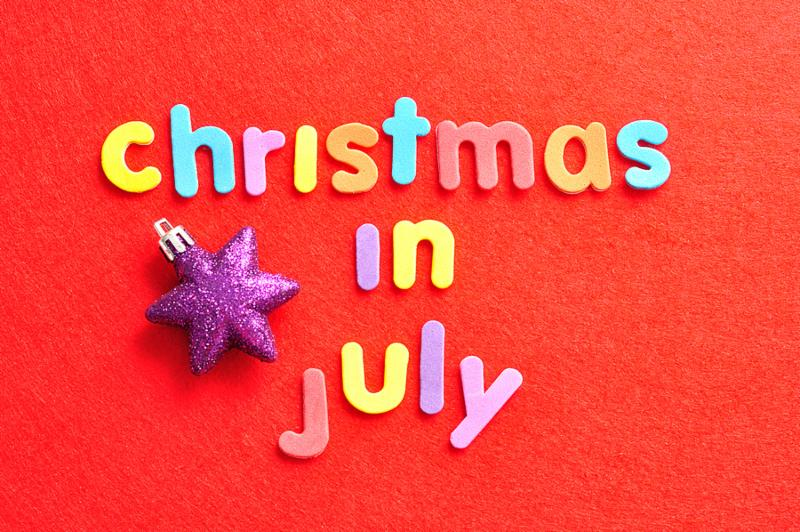The words christmas in July in colorful letters on a red background and a purple star shape Christmas tree bauble