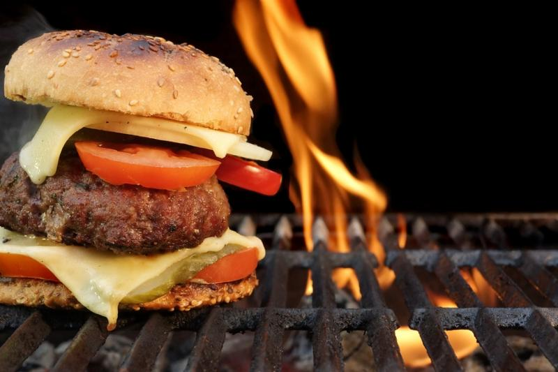 Homemade BBQ Beef Burger On The Hot Flaming Grill. Good Snack For Outdoors Summer Party Or Picnic     Note  Shallow depth of field